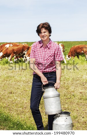 Farmer with milk churns at their cows