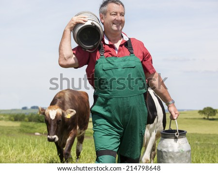 Farmer with milk jug with the cows - stock photo
