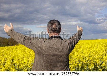 Farmer with outstretched arm at the rape field - stock photo