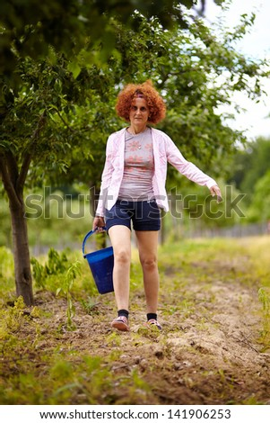 Farmer woman carrying a bucket with fertilizer in an orchard, with selective focus