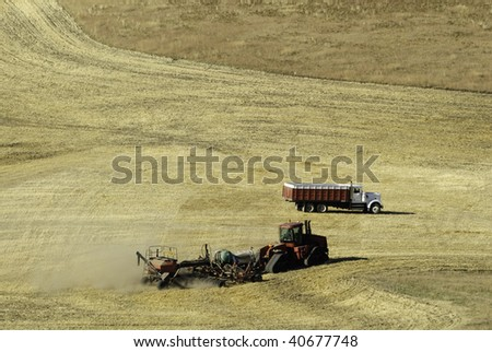 Farmer working the field with tractor. He is tilling and spraying the field in one go around. - stock photo