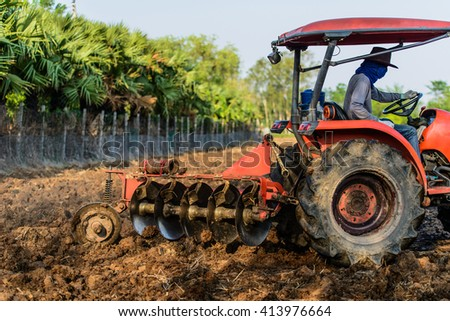 Farmers are driving tractor plowing and sowing in the field