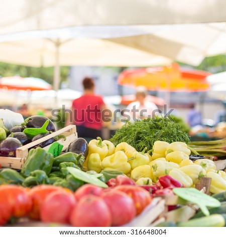 Farmers' food market stall with variety of organic vegetable. Vendor serving and chating with customers. - stock photo