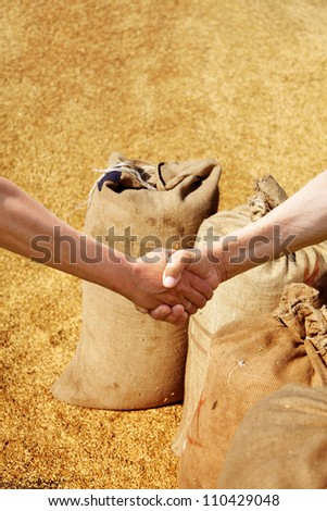 Farmers handshake at sacks background. - stock photo