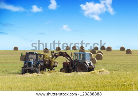 Farmers harvesting hay by tractores in sunny day. - stock photo
