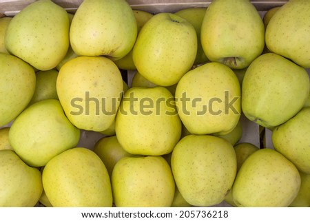 Farmers market apples in a wooden crate background. At the farmers market local growers come and sell their freshly picked crops at reasonable prices. - stock photo