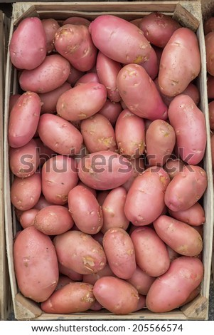 Farmers market red potatoes in a wooden crate background. At the farmers market local growers come and sell their freshly picked crops at reasonable prices. - stock photo