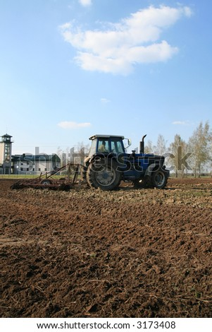 Farmers plowing with tractor in agricultural field