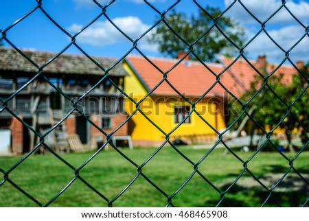 Farmhouse and garden through the chain-link fence that is in focus