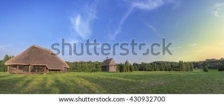 farmhouse green meadow and blue sky - stock photo