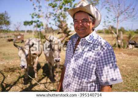 Farming and cultivations in Latin America. Portrait of middle aged hispanic farmer sitting proud in his tractor at sunset, holding the volante. He looks at the camera and smiles happy. - stock photo
