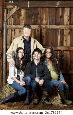 Farming family portrait inside a barn sitting on a bale of hay with two kids and a pregnant mom. - stock photo
