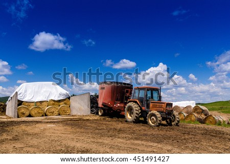farming tractor on land and hay balls