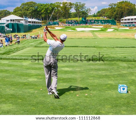 FARMINGDALE, NY - AUGUST 22: Tiger Woods hits a tee shot off the 17th hole at Bethpage Black during the Barclays on August 22, 2012 in Farmingdale, NY. - stock photo