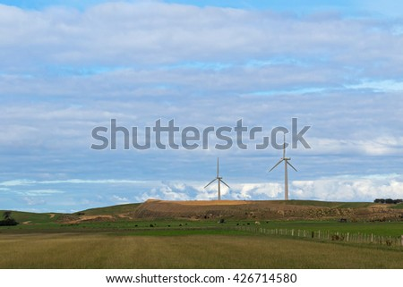 Farmland with cows grazing on meadows and view of huge wind turbines windmill in background, Victoria, Australia