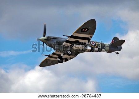 FARNBOROUGH, ENGLAND - JULY 24: A vintage Spitfire fighter plane, in D-Day colour scheme, makes a low flypast for the public at the Farnborough International airshow at Farnborough on July 24, 2010.