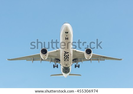 FARNBOROUGH, UK - JULY 14: Airbus 350 XWB, in a clear blue sky, landing at an international aviation trade event at Farnborough, Hampshire, UK on July 14, 2016 - stock photo