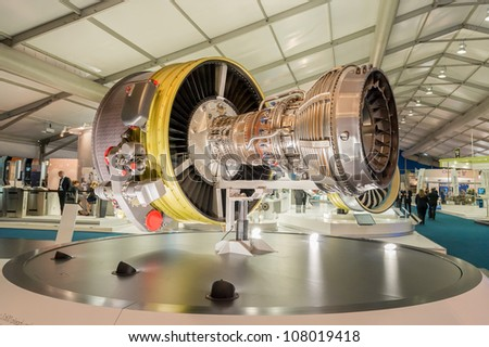 FARNBOROUGH, UK - JULY 12: Exhibition stands displaying large jet engines and other components used in the aviation industry at the Farnborough International Airshow, UK on July 12, 2012 - stock photo