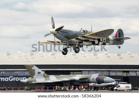 FARNBOROUGH, UK - JULY 24: WW2 Spitfire coming into land with XH558 Vulcan bomber in the background. July 24 2010, Farnborough Airshow, UK. - stock photo