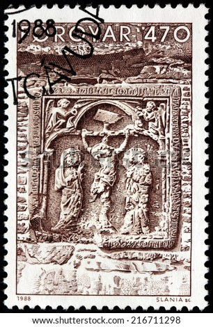FAROE ISLANDS - CIRCA 1988: A stamp printed by FAROE ISLANDS shows stone relief the Crucifixion of Jesus scene over church's reliquary in the Magnus Cathedral in Kirkjubour, circa 1988. - stock photo