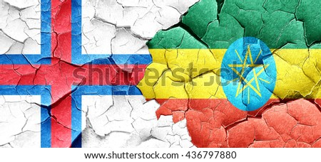 faroe islands flag with Ethiopia flag on a grunge cracked wall - stock photo