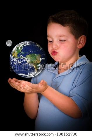 Fascinated and curious child studying the Earth between his hands in education or environment concept, with elements of this image furnished by NASA
