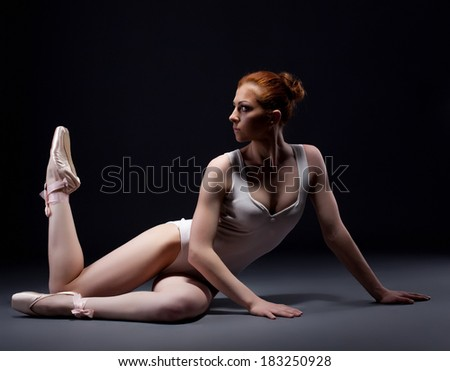 Fascinating red-haired ballerina posing in studio