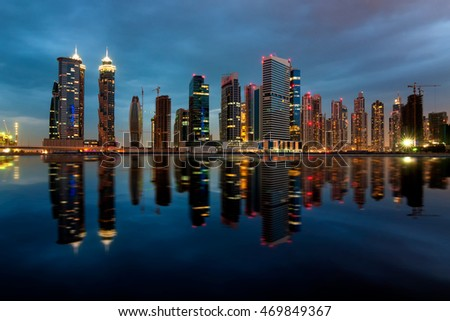 Fascinating reflection of tallest skyscrapers in Business Bay district during cloudy night, Dubai, United Arab Emirates.