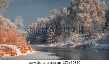 Fascinating winter landscape. Frosty, misty morning on the small river. frost covered trees in the warm glow of sunrise on the beach. The beauty of the world. Eastern Europe. Ukraine - stock photo