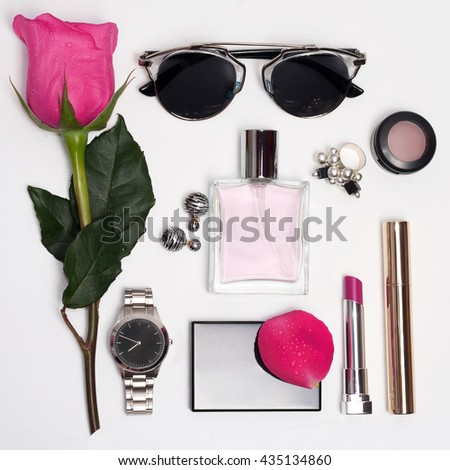 Fashion accessories for woman : watch, sunglasses, lipstick perfume and pink rose on white background. Overhead of essentials for modern young woman. - stock photo