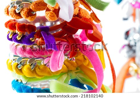 Fashion accessories: very colourful bracelets made by weaving velvet ribbons and metal chains together. White background. - stock photo