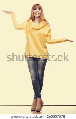 Fashion and advertisement concept. Full length woman holding open palm empty hands showing copy space for product - stock photo