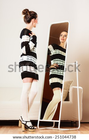 Fashion and shopping. Woman trying dress sweater choosing clothing. Attractive female shopper looking in mirror, standing in clothes store. - stock photo