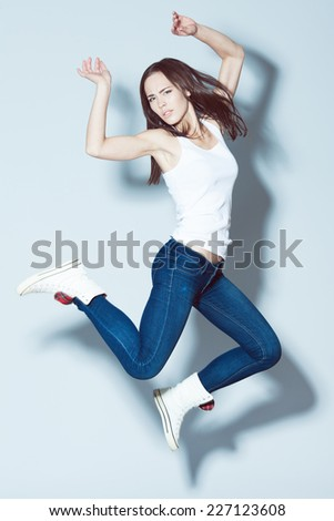 Fashion and sport activity concept. Young fitness model in white blank sleeveless shirt and blue jeans jumping with hands up over light blue background