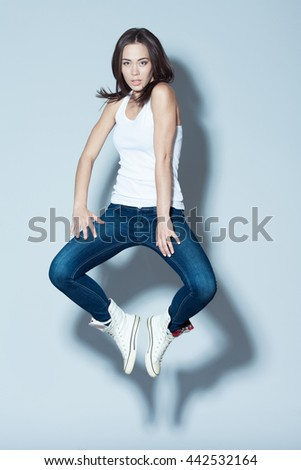 Fashion and sport activity concept. Young fitness model in white blank sleeveless shirt, blue jeans and white footwear  jumping with hands up over light blue background