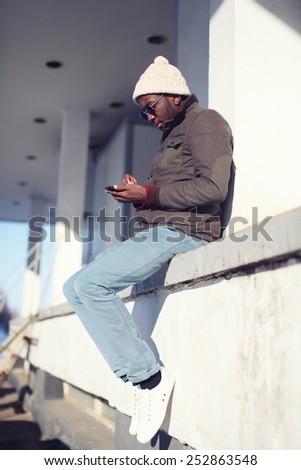 Fashion and technology concept - lifestyle stylish young african man using smartphone in the city  - stock photo