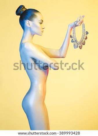 Fashion art photo of elegant nude model in the light colored spotlights - stock photo