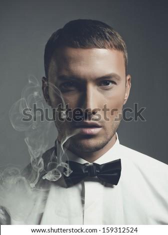 Fashion art portrait of a handsome man smoking - stock photo