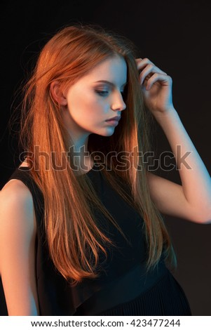 Fashion art portrait of beautiful red haired fashion model girl with long  hair in black dress over dark background, in colorful lighting - stock photo