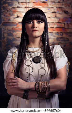 Fashion art portrait of the Queen Cleopatra.Ancient Egypt.Break wall.Magnificent sexy woman in white gold rich dress.Professional make up.Beautiful egyptian bronze brunette woman.Pharaoh Cleopatra - stock photo