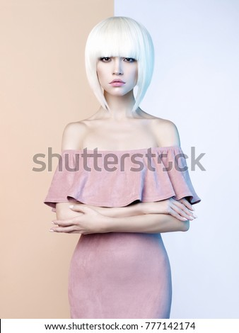 Fashion art studio portrait of elegant blonde in geometric beige and white background. Fashion and style in advertising