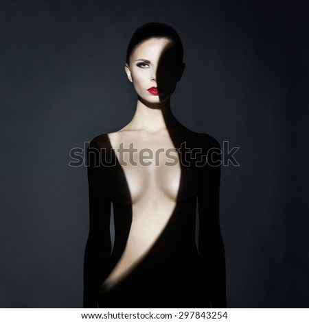 Fashion art studio portrait of elegant naked lady with shadow on her body - stock photo