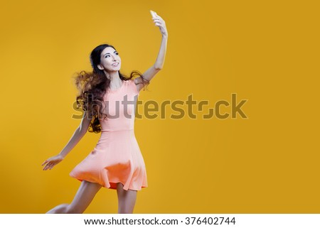 Fashion asian young  girl   taking picture of herself, selfie. Yellow background. place for your text on the right - stock photo