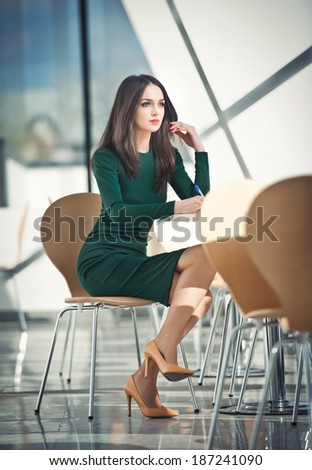 Fashion attractive girl in dark green dress sitting on chair writing, indoor shot. Modern urban scenery. Fashion art photo of sensual lady in glass and steel scenery. Girl with high heels at table