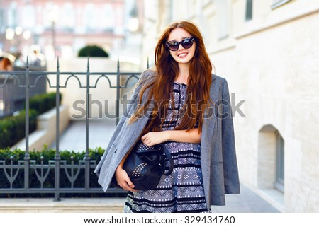 Fashion autumn portrait of stylish ginger woman, posing on the street, feminine tender smart casual outfit, vintage sunglasses, long hairs, street style. holding black leather bag and smiling . - stock photo