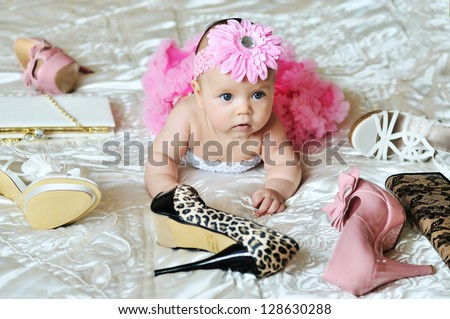 fashion  baby girl laying on the bed with high heels shoes and bags