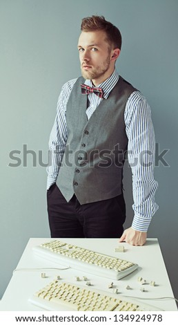 Fashion bearded man in suit and bow tie standing near table with keyboards - stock photo
