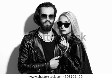 fashion beautiful couple in black leather wearing trendy sunglasses together. Hipster boy and girl. Bearded young man and blonde - stock photo
