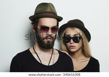 fashion beautiful couple in hat wearing trendy glasses together. Hipster boy and girl. Bearded young man and blonde model in sunglasses - stock photo