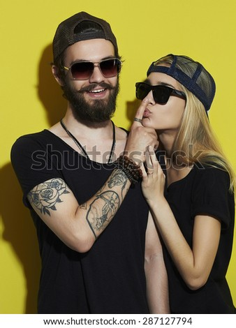 fashion beautiful couple together. Tattoo Hipster boy and girl. Bearded young man and blonde in sunglasses.Yellow background - stock photo